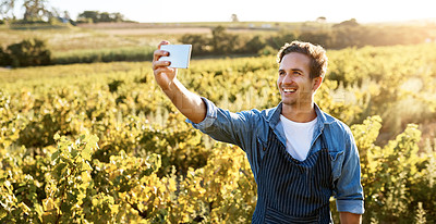 Buy stock photo Shot of a young man taking a selfie with his cellphone while working on a farm