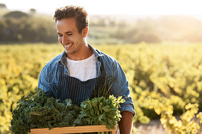 Buy stock photo Shot of a young man holding a crate full of freshly picked produce on a farm