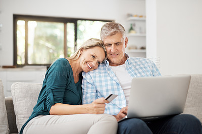 Buy stock photo Cropped shot of an affectionate mature couple using their laptop to do some online shopping at home