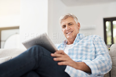Buy stock photo Cropped portrait of a handsome mature man using a tablet while sitting on the sofa at home