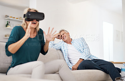 Buy stock photo Cropped shot of a mature woman using a VR headset with her husband in the background