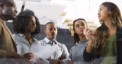 Buy stock photo Cropped shot of a diverse group of businesspeople brainstorming on a glass wall in a modern office