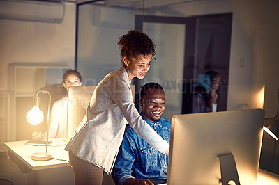 Buy stock photo Shot of two colleagues working late together on a computer in an office