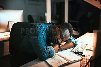 Buy stock photo High angle shot of a young male designer sleeping at his desk while working late in the office