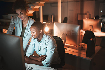 Buy stock photo High angle shot of two young designers working together on a computer in their office