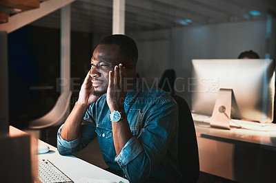 Buy stock photo High angle shot of a young male designer looking stressed while working on his computer in the office