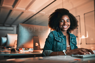 Buy stock photo Low angle portrait of an attractive young female designer working on her computer in the office