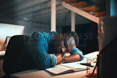 Buy stock photo Cropped shot of a young male designer sleeping at his desk while working late in the office