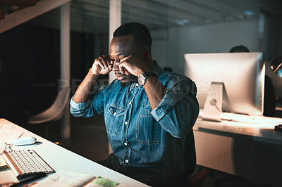 Buy stock photo Cropped shot of a young male designer looking stressed while working on his computer in the office