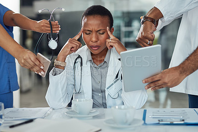 Buy stock photo Shot of a doctor looking stressed out in a demanding work environment
