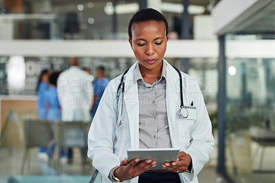 Buy stock photo Shot of a doctor using a digital tablet in a hospital