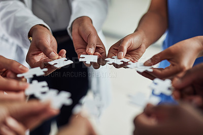 Buy stock photo Closeup shot of an unrecognizable group of medical practitioners joining puzzle pieces together