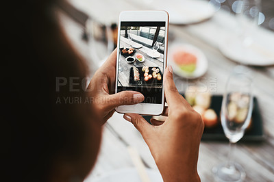Buy stock photo Cropped shot of an attractive young woman using her cellphone while out at a restaurant