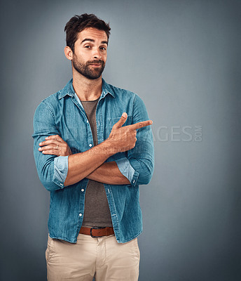 Buy stock photo Studio shot of a handsome young man pointing at copy space against a grey background