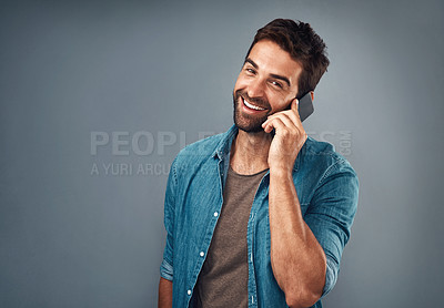 Buy stock photo Studio shot of a handsome young man using a mobile phone against a grey background