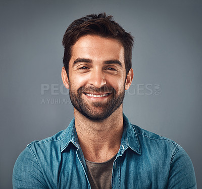 Buy stock photo Studio shot of a handsome and happy young man posing against a grey background