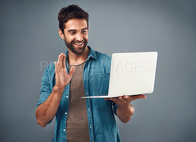 Buy stock photo Studio shot of a handsome young man using a laptop and waving against a grey background