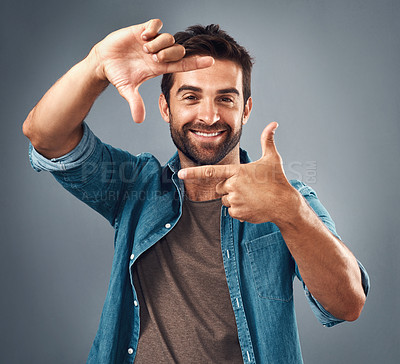 Buy stock photo Studio portrait of a handsome young man making a finger frame against a grey background
