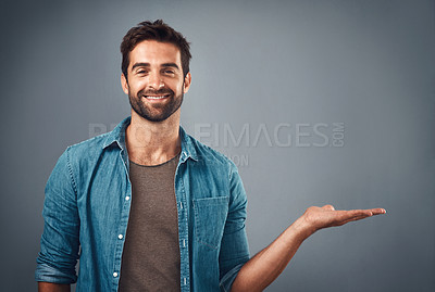 Buy stock photo Studio shot of a handsome young man showing copy space against a grey background