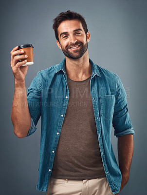 Buy stock photo Studio shot of a handsome young man drinking a cup of coffee against a grey background