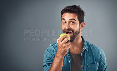Buy stock photo Studio shot of a handsome young man eating an apple against a grey background