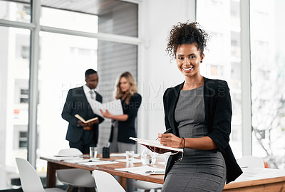 Buy stock photo Portrait of a young businesswoman using a digital tablet in an office with her colleagues in the background
