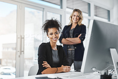 Buy stock photo Portrait of two businesswomen working together in an office