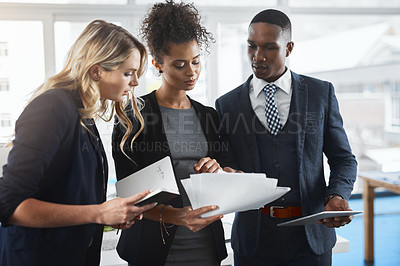 Buy stock photo Shot of a group of businesspeople going through paperwork together in an office