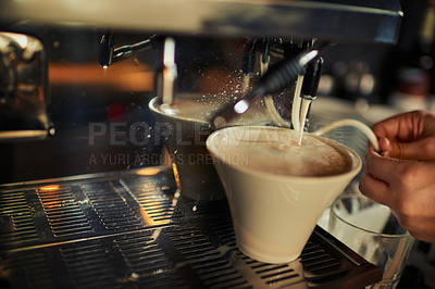 Buy stock photo Closeup of an unrecognizable person pouring hot milk into a cup of coffee inside of a restaurant during the day