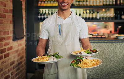 Buy stock photo Shot of an unrecognizable waiter holding three plates of food that he's going to serve to customers inside of a restaurant during the day