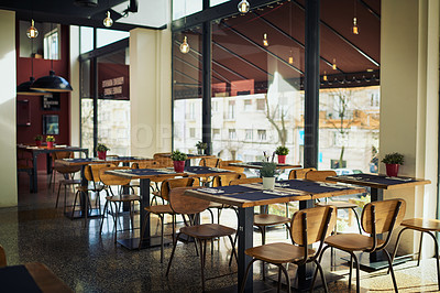 Buy stock photo Shot of an empty restaurant filled with tables and chairs inside during the day
