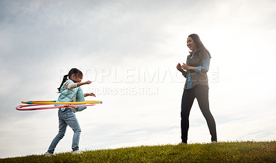 Buy stock photo Shot of a mother watching her daughter spinning the hula hoop