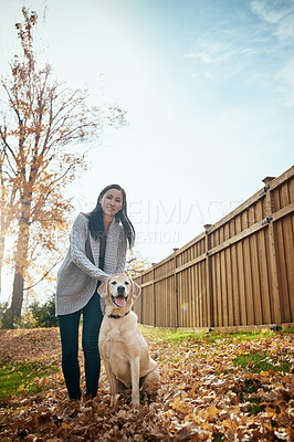 Buy stock photo Portrait of an attractive young woman having fun with her dog on an autumn day in a garden