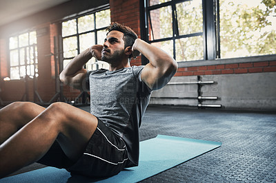 Buy stock photo Shot of a handsome young man working out at the gym