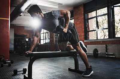 Buy stock photo Shot of a young man working out with dumbbells at the gym