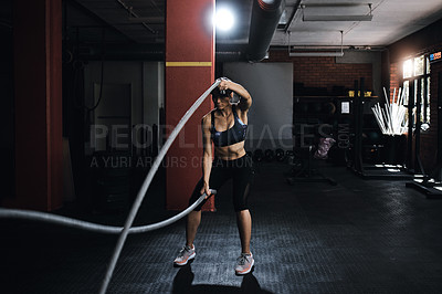 Buy stock photo Shot of a young woman doing heavy rope training at the gym