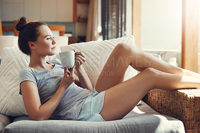 Buy stock photo Shot of an attractive young woman enjoying her morning coffee while relaxing on the sofa at home