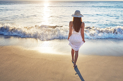 Buy stock photo Rearview shot of an unrecognizable woman spending the day at the beach