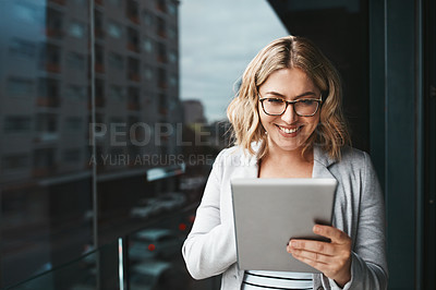 Buy stock photo Shot of a young businesswoman using a digital tablet on the office balcony