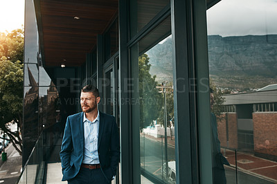 Buy stock photo Shot of a mature businessman standing on the office balcony
