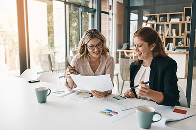 Buy stock photo Shot of two businesswomen going through paperwork together in an office