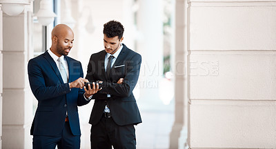 Buy stock photo Cropped shot of young handsome businessmen using a cellphone together outside