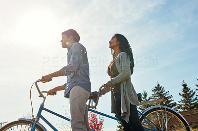 Buy stock photo Shot of a young couple out for a ride on a tandem bicycle