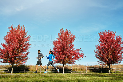 Buy stock photo Shot of a sporty young couple exercising together outdoors
