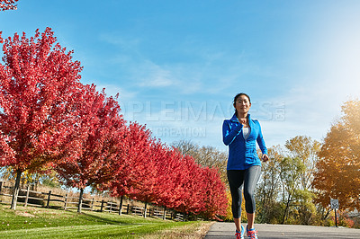 Buy stock photo Shot of a sporty young woman running outdoors