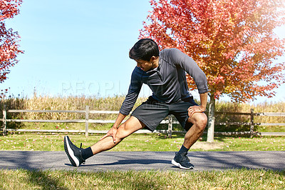 Buy stock photo Shot of a sporty young man stretching his legs while exercising outdoors