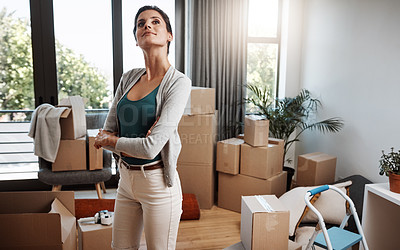 Buy stock photo Cropped shot of an attractive young woman standing with her arms folded while moving into a new house