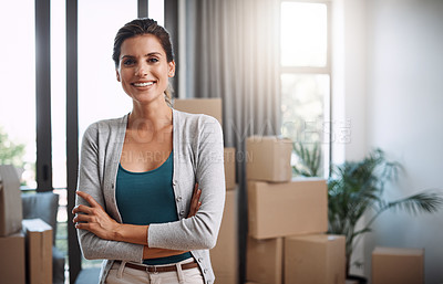 Buy stock photo Cropped portrait of an attractive young woman standing with her arms folded while moving into a new house
