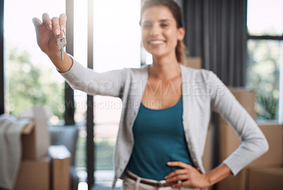 Buy stock photo Cropped shot of an attractive young woman holding the key to her new home while moving in