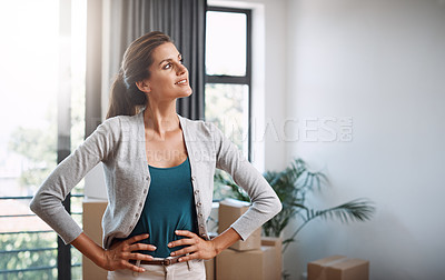 Buy stock photo Cropped shot of an attractive young woman standing with her hands on her hips while moving into a new house